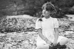 Vintage thoughtful girl. Young girl in a leaf crown sitting cross legged with a contemplative expression Stock Images