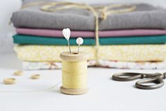 Vintage thread spool, pins, scissors and cotton fabrics royalty free stock photos