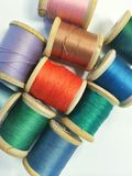 Vintage Thread. On wooden spools in various colors on white backdrop stock photos