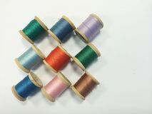 Vintage Thread. On wooden spools in various colors on white backdrop royalty free stock images