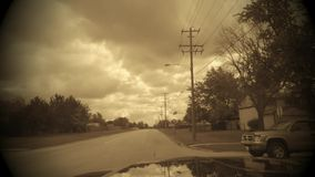 Vintage time lapse car interior driving down road looking out front windshield on a cloudy day. A car ride down road in residential suburban neighborhood looking stock video footage