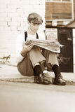 Vintage Times. Vintage Man Sits On A Curbside To Read The Not So Latest News In The Vintage Times Stock Image