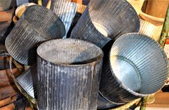 Unusual weathered vintage containers. Vintage tin containers loosely stacked in a metal basket at a New Hampshire farm stand Stock Image
