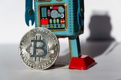 Vintage tin toy robot with bitcoin coin, cryptocurrency mining concept stock images