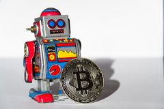 Vintage tin toy robot with bitcoin coin, cryptocurrency mining concept royalty free stock photography