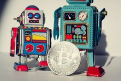 Vintage tin toy robot with bitcoin coin, cryptocurrency mining concept stock photos