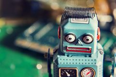 Vintage tin toy robot with computer board, artificial intelligence concept. Vintage tin toy robot with green computer circuit board background, artificial Stock Photography