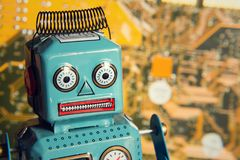 Vintage tin toy robot with computer circuit board background, artificial intelligence concept Royalty Free Stock Image