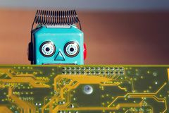 Vintage tin toy robot behind computer board, artificial intelligence concept royalty free stock photos