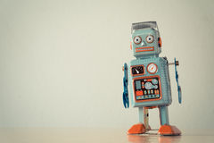 Vintage tin toy robot. On wooden table royalty free stock image