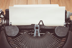 Vintage tone of Antique typewriter with aged paper sheet Stock Photo