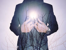 Vintage tone ,double exposure, businessman with dry branches against sun Stock Photo