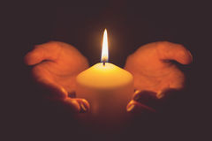 Vintage tone of hands holding a burning candle in dark Royalty Free Stock Photos