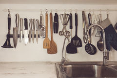 Vintage tone of Kitchen cooking utensils on rack Stock Image