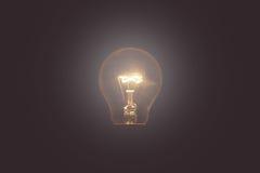 Vintage tone of Light bulb turned on over black background Stock Photo