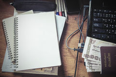 Vintage tone, messy working table, with blank notebook, passport, cash, laptop, and etc. Stock Photos