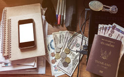 Vintage tone, messy working table, with cash, passport, smartphone, laptop, and etc. Stock Photo