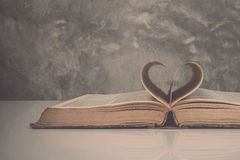 Vintage tone of Pages of a book forming the shape of the heart. Stock Photos