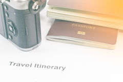 Vintage tone passport and camera on travel itinerary paper. royalty free stock photos