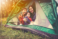 Vintage tone photo of happy family looking at camera on camping. Vintage tone photo of happy asian family looking at camera on camping trip in their tent stock image