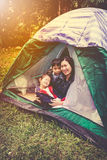 Vintage tone photo of happy family looking at camera on camping. Vintage tone photo of happy asian family looking at camera on camping trip in their tent royalty free stock photo