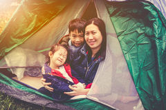 Vintage tone photo of happy family looking at camera on camping. Vintage tone photo of happy asian family looking at camera on camping trip in their tent stock images