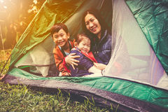 Vintage tone photo of happy family looking at camera on camping Stock Photo