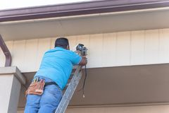 Rear view of technician installing surveillance camera on roof. Vintage tone rear view of technician installing surveillance camera on roof. Latino handyman on Royalty Free Stock Images
