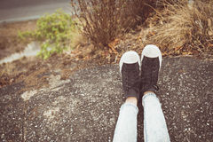 Vintage tone of Shoes of a girl sitting on the edge of a cliff Royalty Free Stock Images