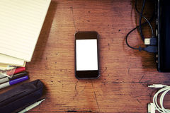 Vintage tone, Smartphone on messy antique wooden table, working space Royalty Free Stock Images
