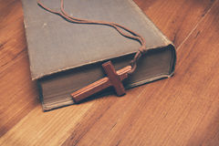 Vintage tone of wooden Christian cross necklace on holy Bible Royalty Free Stock Photos