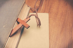 Vintage tone of wooden Christian cross necklace on holy Bible royalty free stock photography