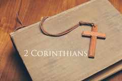 Vintage tone of wooden Christian cross necklace on holy Bible wi. A Vintage tone of wooden Christian cross necklace on holy Bible with 2 Corinthians Royalty Free Stock Image