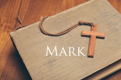 Vintage tone of wooden Christian cross necklace on holy Bible wi. A Vintage tone of wooden Christian cross necklace on holy Bible with Mark Stock Image