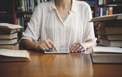 Vintage tone of Young female student with tablet in book store Stock Image