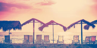 Vintage toned beach chairs and umbrellas at sunset, holidays bac Stock Images