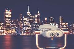 Vintage toned binoculars with New York skyline at night, USA. Vintage toned binoculars with New York City skyline at night, USA Stock Photos