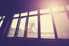Vintage toned coal mine pithead seen through windows. Royalty Free Stock Image