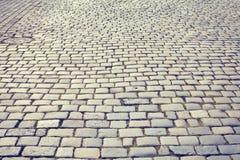 Vintage toned cobblestone street. Vintage toned cobblestone street in Poznan, Poland royalty free stock image