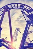 Vintage toned cranes behind roller coaster rails at sunset Stock Photos