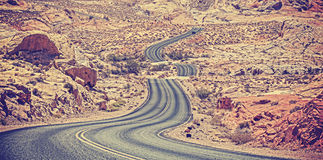 Vintage toned curved desert highway. Royalty Free Stock Image