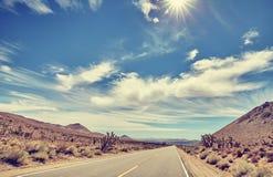Vintage toned desert road against sun, travel concept. Stock Image