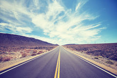 Vintage toned desert road in Death Valley, travel concept. Royalty Free Stock Photography