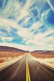 Vintage toned desert road in Death Valley. Stock Photos