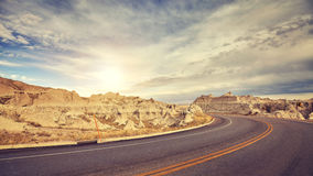Vintage toned desert road just before sunset, travel concept. Stock Photos