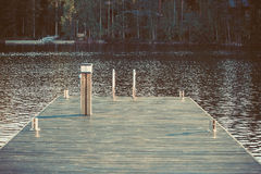 Vintage toned dock or pier on lake in summer day. forest,  Finland Royalty Free Stock Photos