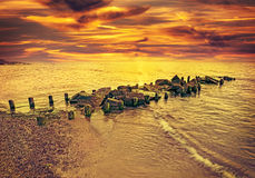 Vintage toned dramatic sunset over beach and rocky pier Stock Image