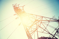 Vintage toned electricity transmission tower. Vintage toned electricity transmission tower against sun at sunset royalty free stock photos