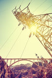 Vintage toned electricity transmission tower. Vintage toned electricity transmission tower against sun at sunset stock photos