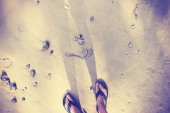 Vintage toned female feet in flip flops on sand. Royalty Free Stock Photo